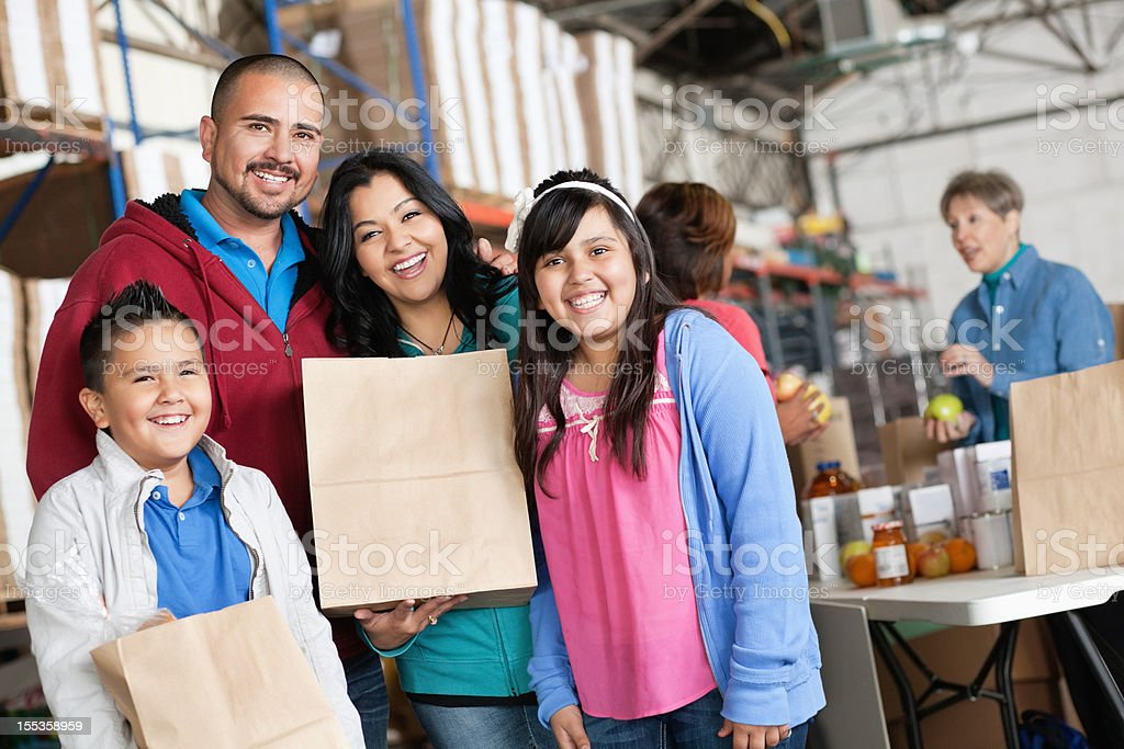 Family holding donations at a food donation bank royalty-free stock photo