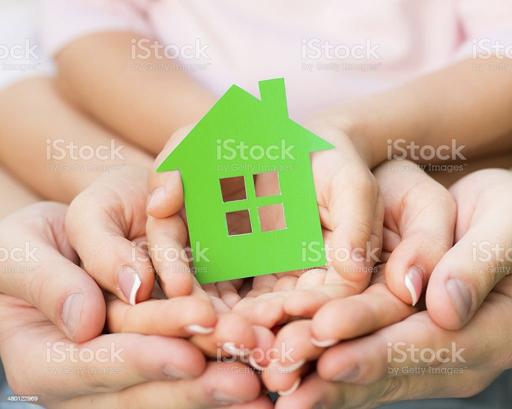 Family holding green paper house stock photo