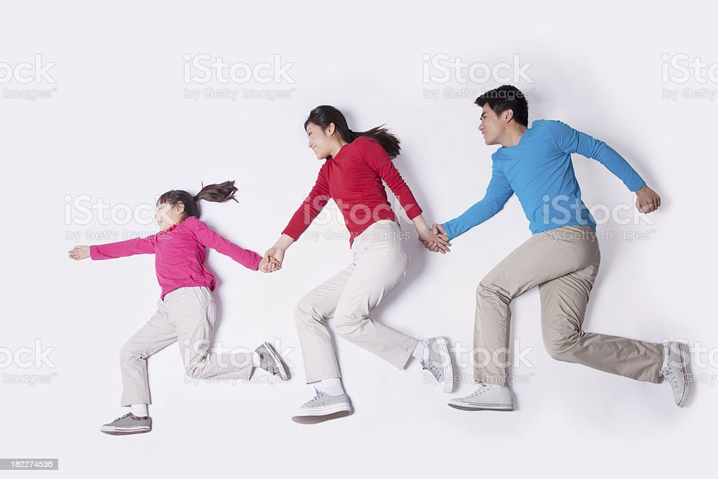 Family holding hands and imitating running, studio shot stock photo