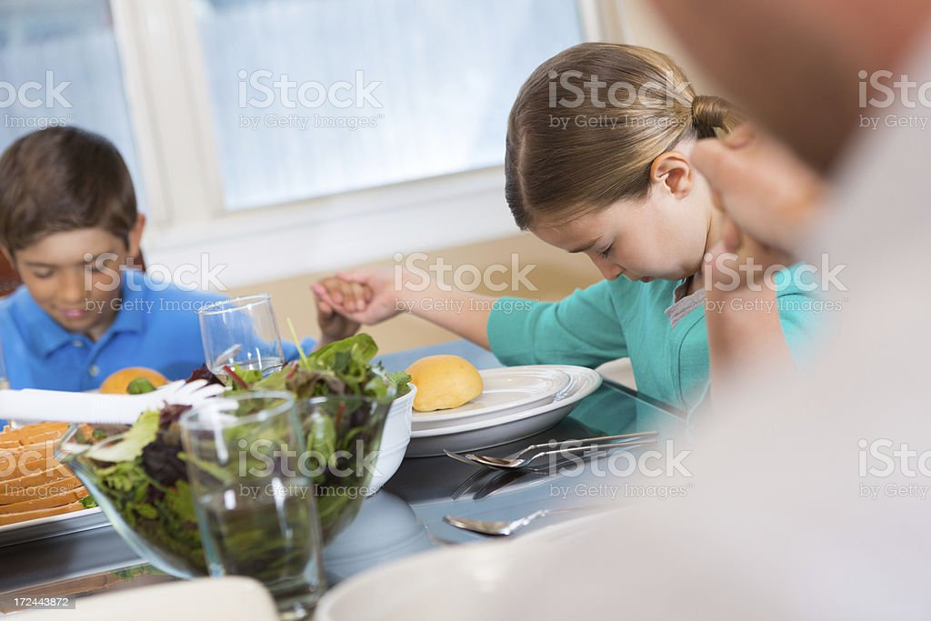 Family holding hands and praying over Thanksgiving meal royalty-free stock photo