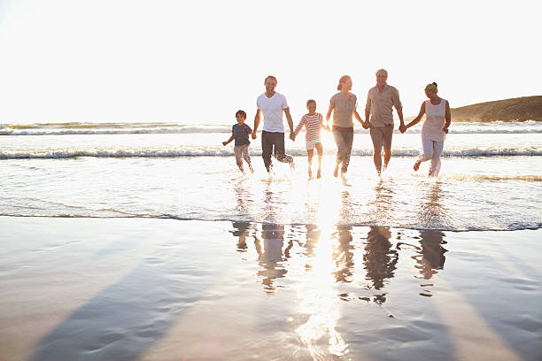 family holding hands in water at beach - distant stock photos and pictures