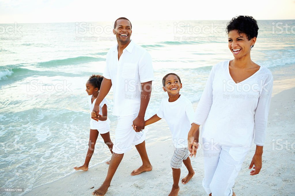 Family holding hands walking on beach stock photo