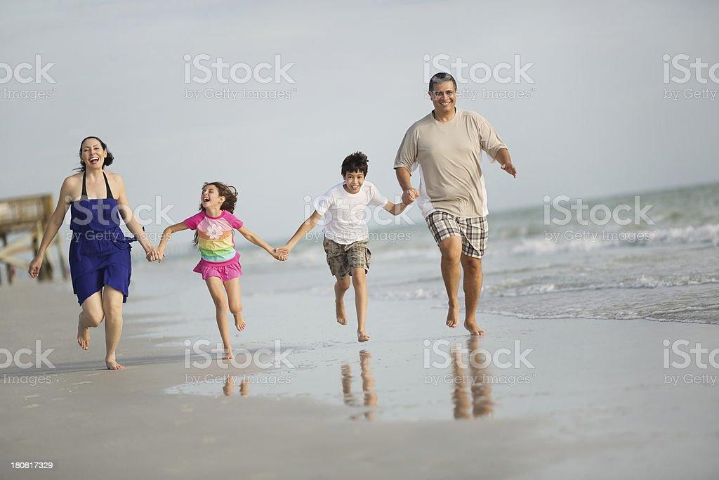 Familie halten Ihre Hände beim Laufen am Strand – Foto
