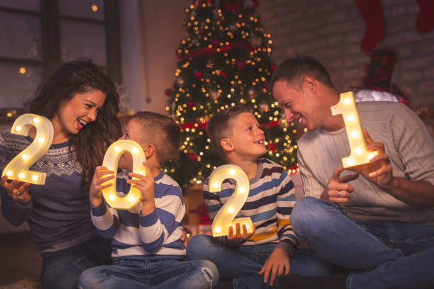 Family holding numbers 2021 Parents celebrating New Years Eve at home with kids, sitting by the Christmas tree, holding illuminative numbers 2021 representing the upcoming New Year happy new year 2021 stock pictures, royalty-free photos & images