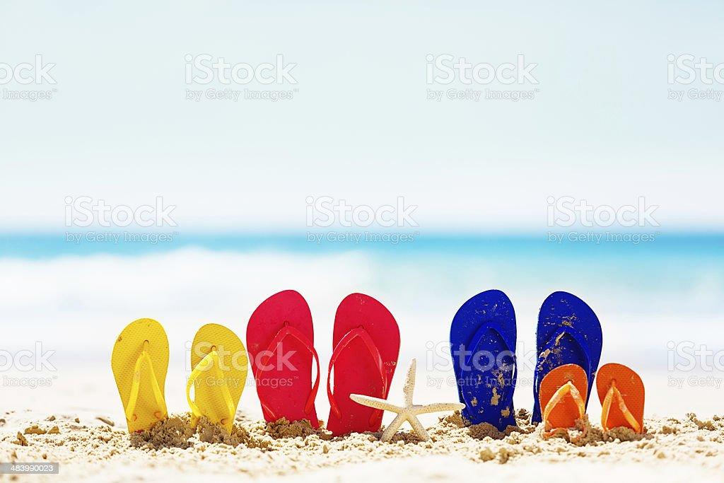 Family holiday fun! Flipflops on the beach. stock photo