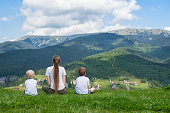 Family holiday. Mother and two sons admire the view of the mountain. Back view. Sunny summer day
