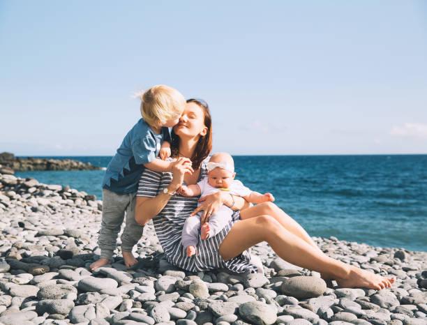 Vacaciones en familia en Tenerife, España. Madre con niños al aire libre en el océano. - foto de stock