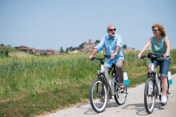 Family holidays in Langhe region, Piedmont, Italy: Electric bikes trip in the hills Family holidays in Langhe region, Piedmont, Italy: Electric bikes trip in the hills electric bike stock pictures, royalty-free photos & images