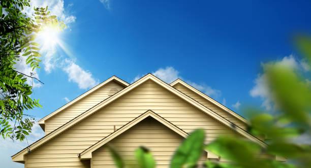 family home exterior over sunny blue sky stock photo
