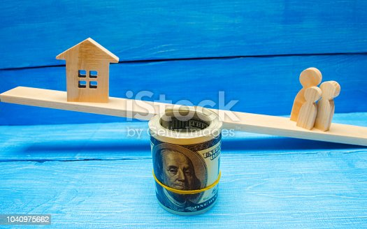 istock family, house and dollars on the scales/ balance. buying selling renting a house and an apartment. credit mortgage property tax. investment in real estate. saving money Home loan 1040975662