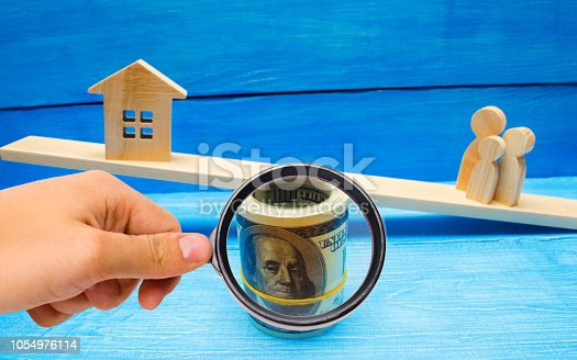 istock family, house and dollars on the scales/ balance. buying selling renting a house and an apartment. credit mortgage property tax. investment in real estate. saving money Home loan 1054976114