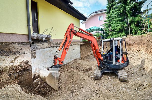 family house is being rebuilt with the help of excavator - graven stockfoto's en -beelden