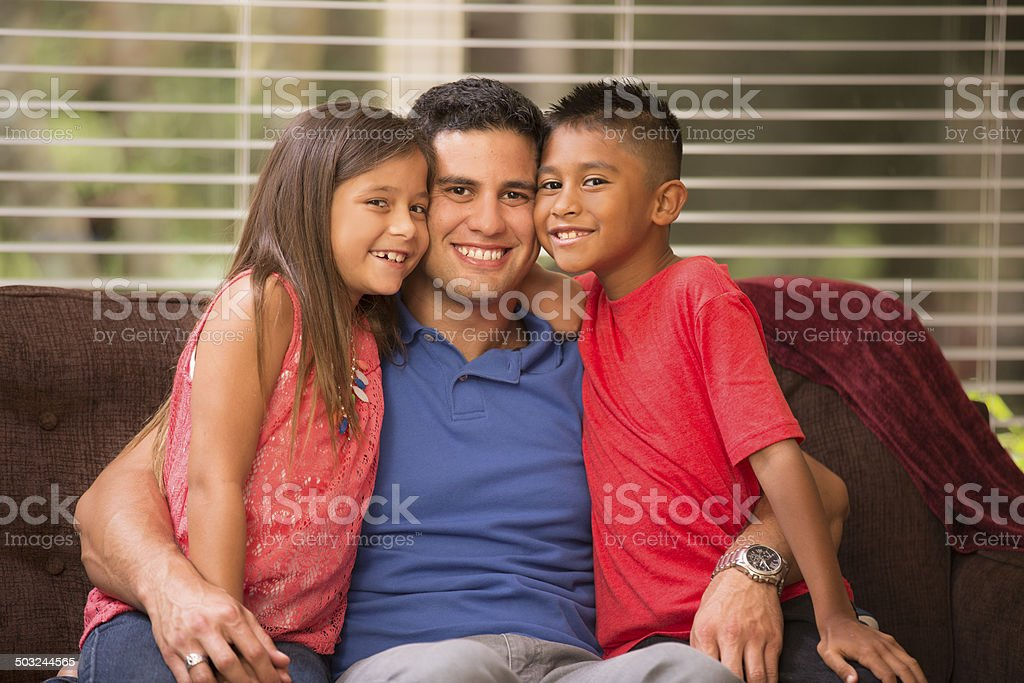 Family hug! Hispanic father, children hug at home. Love, affection. stock photo