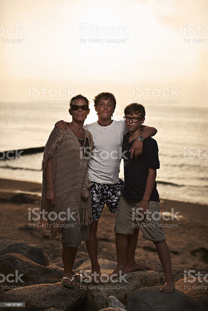 Family hugging on beach stock photo