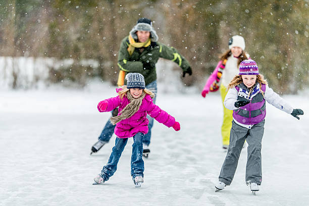 Family Ice-Skating on Pond A family ice-skating on a frozen pond on a snowy day. ice skating stock pictures, royalty-free photos & images
