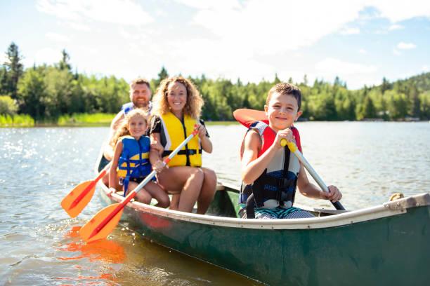 familie in einem kanu auf dem see, spaß - wasser sicherheitsausrüstung stock-fotos und bilder