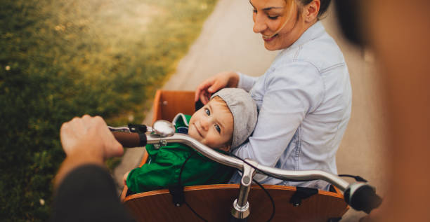 Family in a cargo bike Photo of a cheerful little family who enjoys spending time together, riding in a cargo bicycle // wide photo dimensions // first person perspective personal perspective stock pictures, royalty-free photos & images