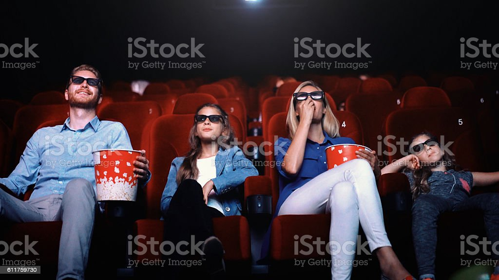 Family in a movie theater.​​​ foto