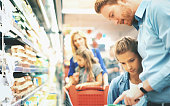Closeup side view of young family with two daughters buying some frozen food in a supermarket. They are at refrigerated section and picking some frozen vegetables. Closeup on one of the daughters and father reading nutrition label on an unrecognizable product.