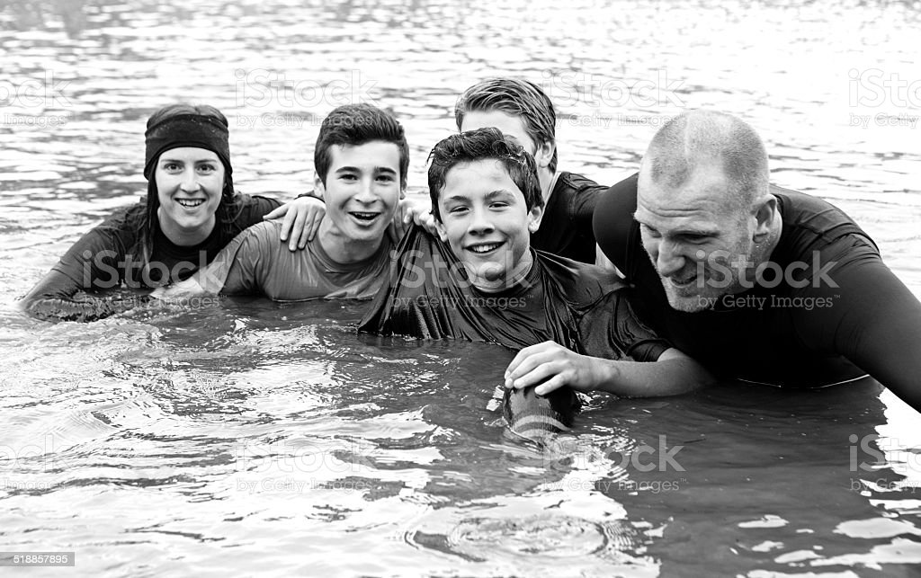 family in a water obstacle at mud run event stock photo