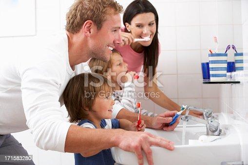 Family In Bathroom Brushing Teeth Together