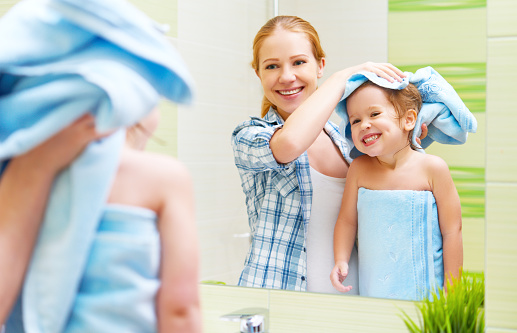istock family in bathroom. mother of child with towel dry hair 506585616