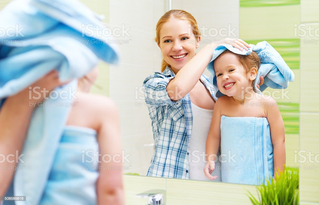 family in bathroom. mother of child with towel dry hair stock photo