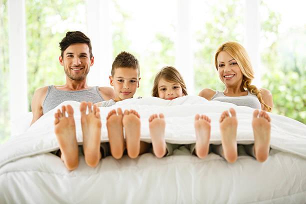 Family in bed showing feet under duvet - foto de stock