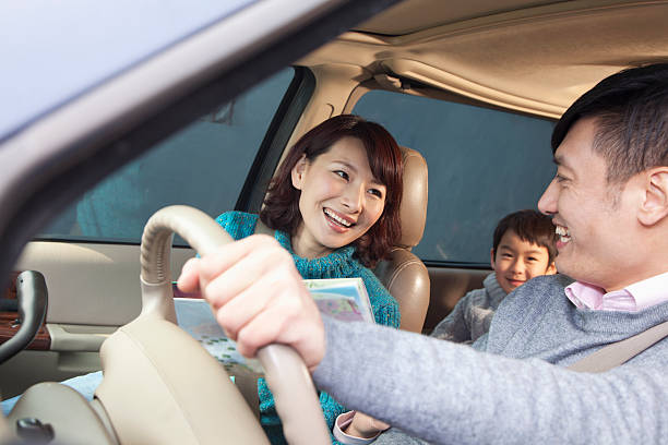 Family in Beijing sitting in a car, laughing stock photo