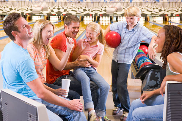 Family in bowling alley with two friends cheering stock photo