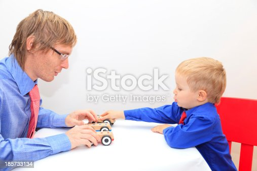 496487362istockphoto family in business style playing toy cars 185733134