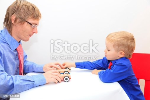 496487362istockphoto family in business style playing toy cars 186144968
