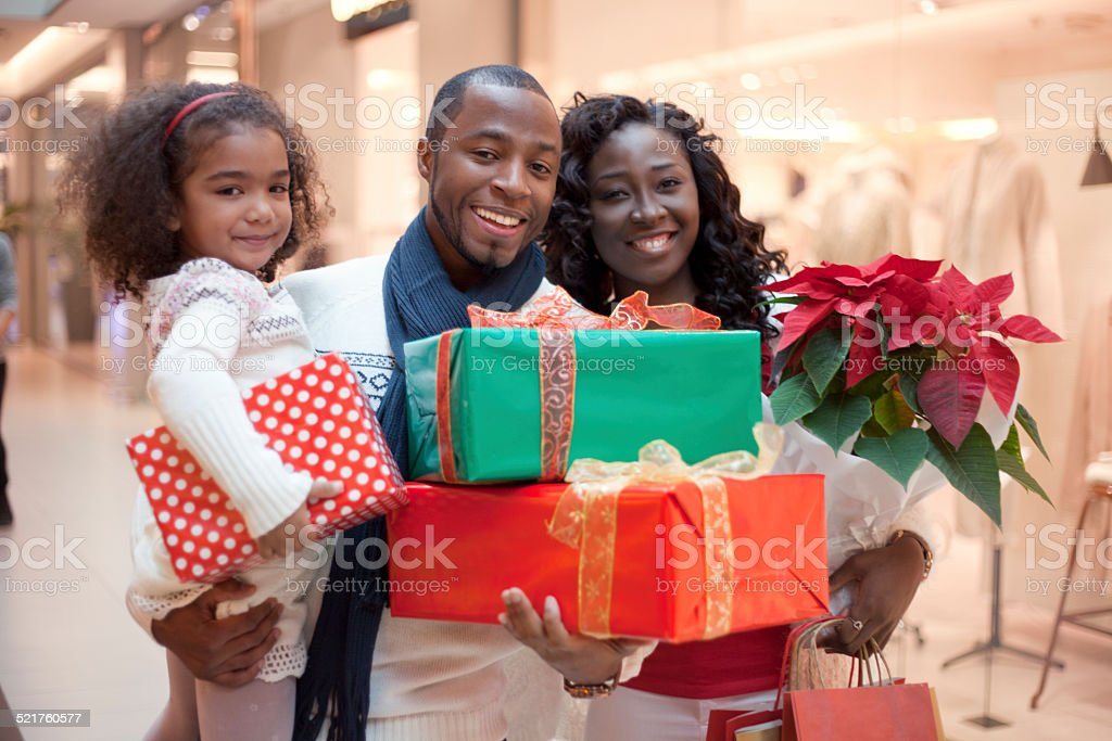Happy family with Christmas gifts shopping at shopping mall
