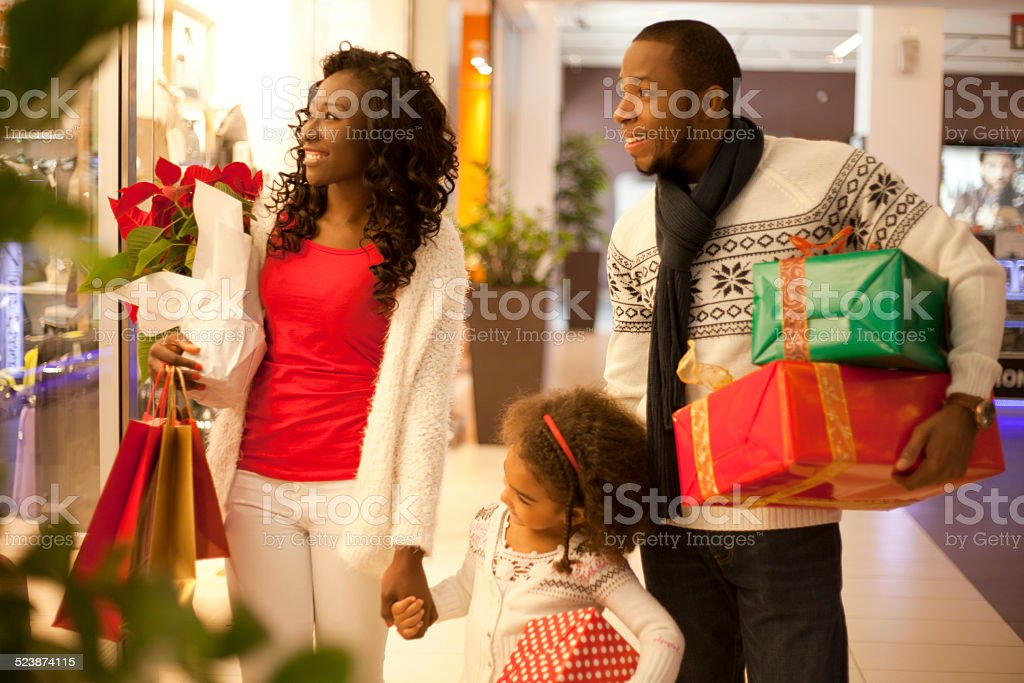 Happy family in Christmas shopping at shopping mall looking at...
