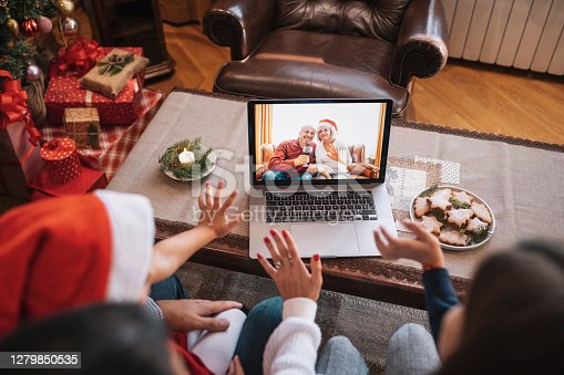 Unrecognizable family and their children wave with hand in video call on Christmas.
