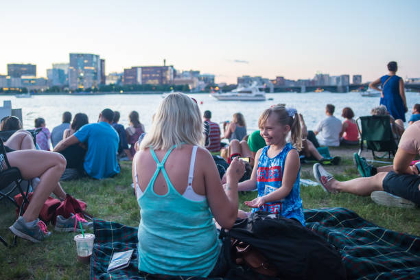 Family in Esplanade Park in Boston for Pops concert Boston, MA, July 3, 2017: Young girl laughs with her mother while sitting on the grass in Esplanade Park and listening to the annual Boston Pops practice concert for July 4th, a Boston tradition. family 4th of july photos stock pictures, royalty-free photos & images