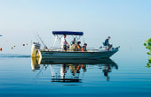 Family in fishing boat on very calm water where the ocean blends into the sky off Cudjoe Key Florida USA circa August 2010