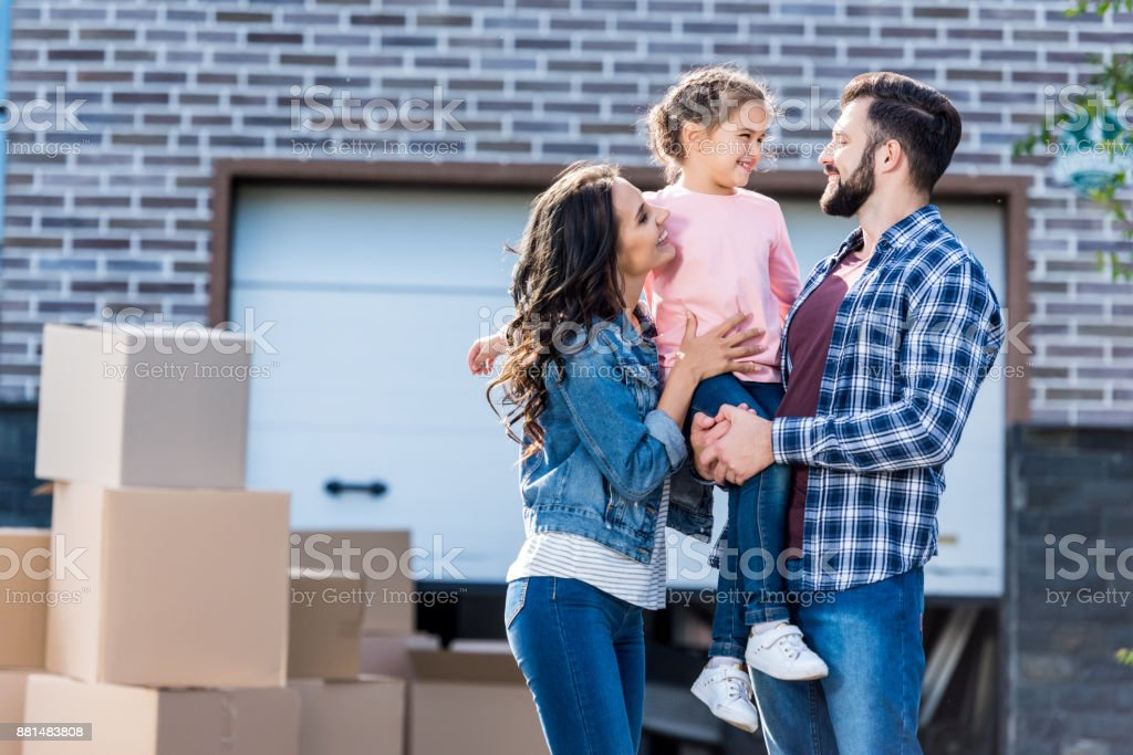 family in front of new house stock photo