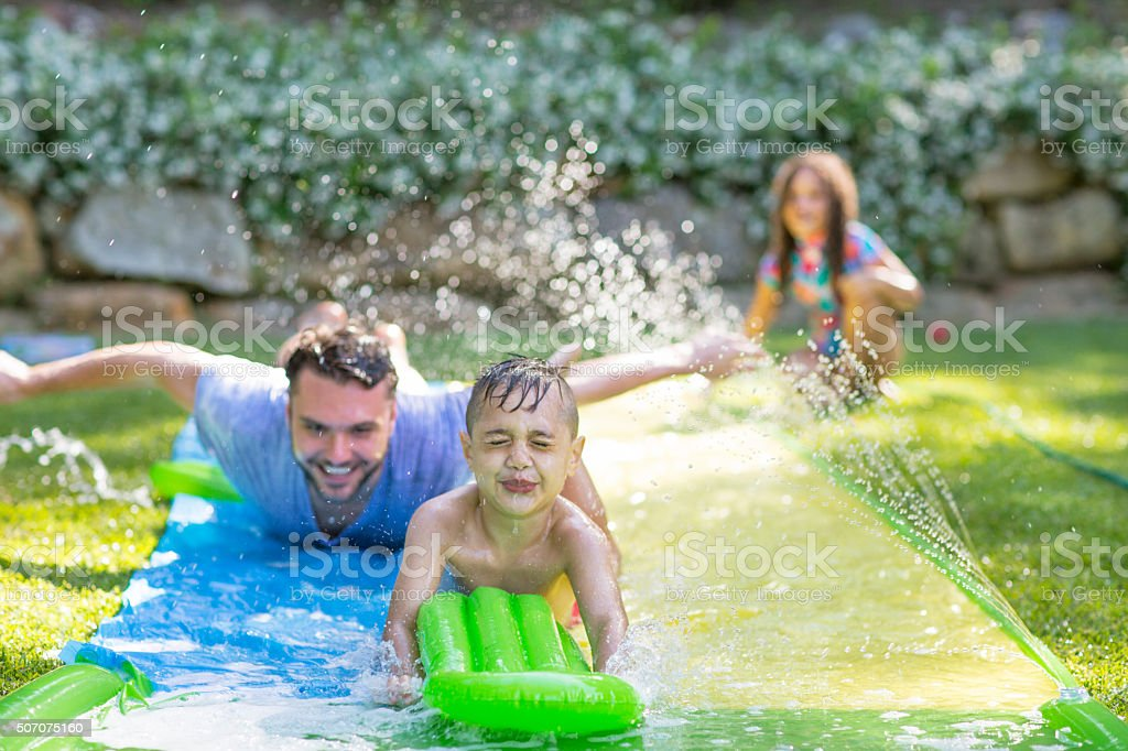 Family in garden playing water games stock photo