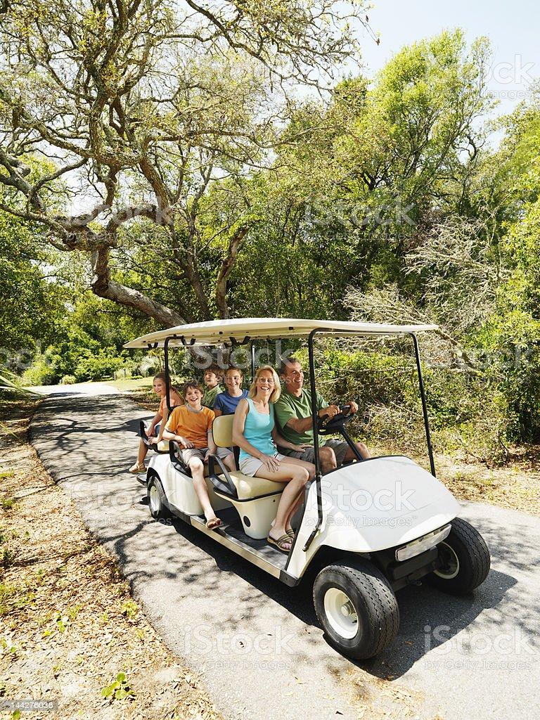 Famille dans une voiturette de golf. - Photo