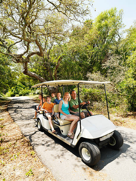 Family in golf cart. Caucasian family riding on golf cart on trail in North Carolina, USA. golf cart stock pictures, royalty-free photos & images
