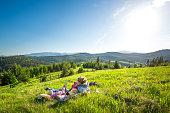 Сute family in green summer meadow near forest in Carpathian mountains
