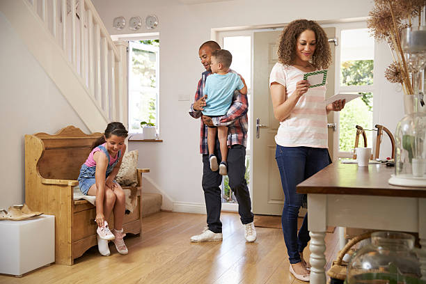 family in hallway returning home together - mail stock photos and pictures