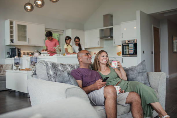 family in holiday cottage - family watching tv stock photos and pictures