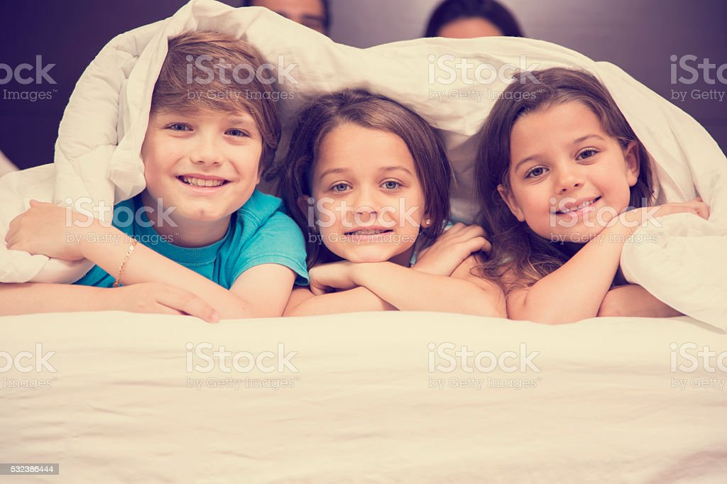Family in hotel bedroom. Happy children on bed. Vacation, tourism. stock photo