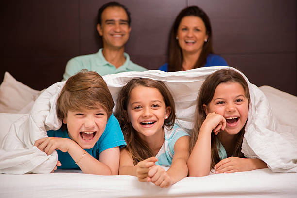 family in hotel room. children foreground on bed. vacation. happy. - cosy pillows mother child bildbanksfoton och bilder