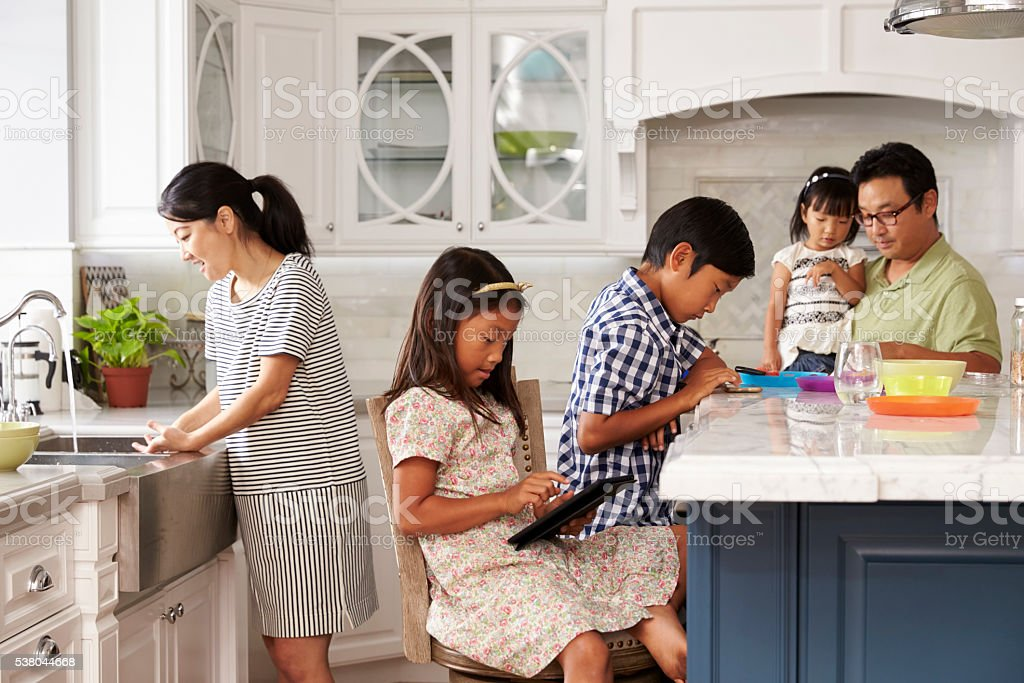 Family In Kitchen Doing Chores And Using Digital Devices stock photo