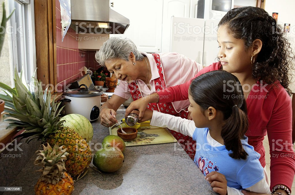 Family in kitchen, grandmother helping granddaughters (6-12) measure spice stock photo