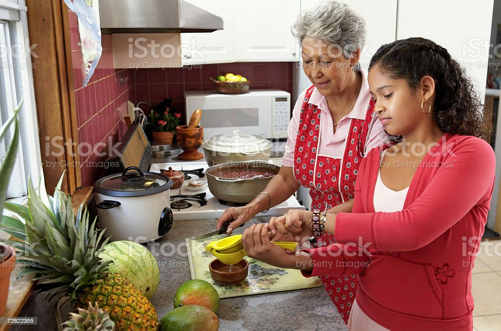 Family in kitchen, grandmother watching granddaughter (10-12) squeezing lime stock photo