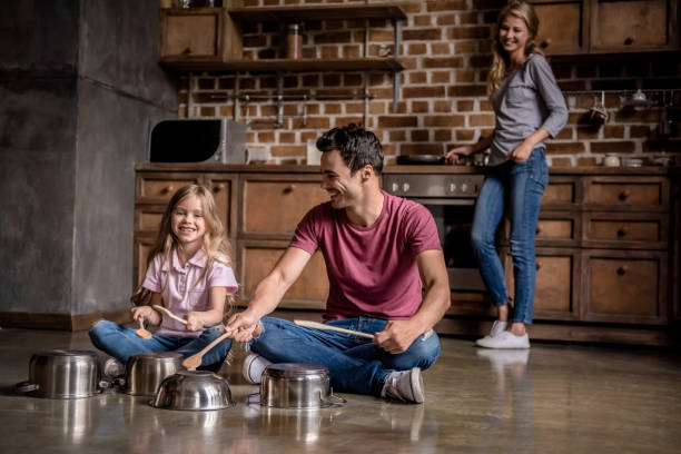 Family in kitchen Cute little girl and her dad are using wooden spoons and smiling while playing drums with dishes in kitchen, mom is cooking percussion instrument stock pictures, royalty-free photos & images